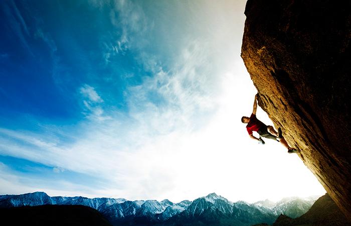 Mountain climber ascending steep cliff